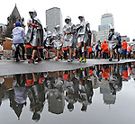 Reflected Runners - Runners wrapped in ponchos try to warm up as they walk along Boylston Street after finishing  the 2015 Boston Marathon in Boston on Monday, April 20, 2015. Photo by Christopher Evans