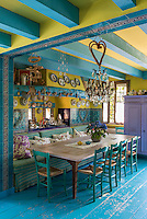 The dining area in the turquoise and yellow painted kitchen features a scrubbed wooden table flanked by a built-in upholstered banquette