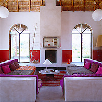 Under the high beamed ceiling in the living room two seating areas have been constructed out of concrete and covered with brilliantly coloured textiles and cushions