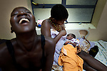 A child prostitute nurses her newborn child for the first time in the Juba. Rapid urbanization and little social infrastructure has resulted in big city problems in the small capital.