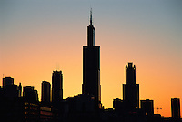 "The WIllis Tower at sunrise. The architecture of Chicago has influenced and reflected the history of American architecture. The city of Chicago, Illinois features prominent buildings in a variety of styles by many important architects. Since most buildings within the downtown area were destroyed by the Great Chicago Fire in 1871, Chicago buildings are noted for their originality rather than their antiquity..Beginning in the early 1880s, architectural pioneers of the Chicago School explored steel-frame construction and, in the 1890s, the use of large areas of plate glass. These were among the first modern skyscrapers and amongst their most famous architects were William LeBaron, John Wellborn Root Sr., Daniel Burnham and Charles Atwood. Louis Sullivan was perhaps the city's most philosophical architect. Realizing that the skyscraper represented a new form of architecture, he discarded historical precedent and designed buildings that emphasized their vertical nature. This new form of architecture, by Jenney, Burnham, Sullivan, and others, became known as the ""Commercial Style,"" but it was called the ""Chicago School"" by later historians..Since 1963, a ""Second Chicago School"" emerged, largely due to the ideas of structural engineer Fazlur Khan. Some of Chicago's skyscrapers such as the John Hancock Center, Willis Tower (formerly known as the Sears Tower) and The Trump International Hotel and Tower are amongst the tallest buildings in the world."