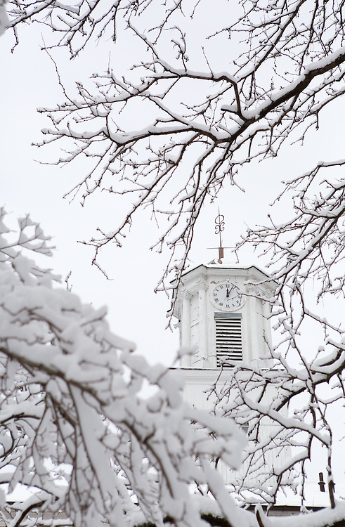 The clock tower of Ohio University's Cutler Hall appears through snow-laden branches on Feb. 3, 2014, when classes were canceled due to inclement winter weather. Photo by Lauren Pond