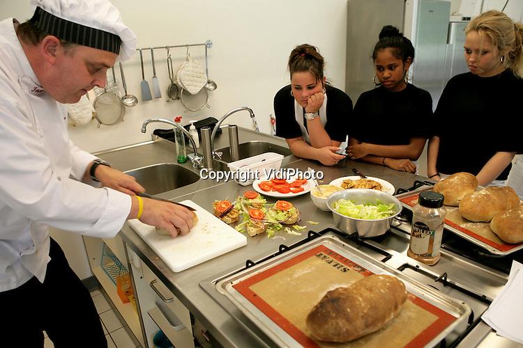 """Foto: VidiPhoto..BEMMEL - Topkok Inno Venhorst van Herberg De Engel uit Dodewaard heeft maandag samen met leerlingen van de Joannesschool in Bemmel -een school voor speciaal voortgezet onderwijs- de leiding over genomen van de kantine tijdens het landelijke project """"Adopteer een kok"""", onderdeel van de Week van de Smaak. Omdat in de meeste schoolkantines nauwelijks een gezonde lunch te krijgen is, helpen koks deze week in heel Nederland met het maken van broodjes gezond, met als basis streekproducten en biologische voeding."""