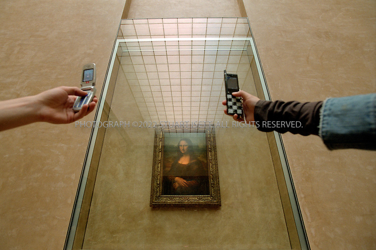 4/7/2005--Paris, France..Visitors to the Louvre Museum in Paris use mobile phone cameras to photograph the 'Mona Lisa' painting, behind a protective glass. The 500-year-old painting is in a new home in the Louvre's Salle des Etats, which has undergone a four-year, a $6.1 million makeover...All photographs ©2005 Stuart Isett.All rights reserved.