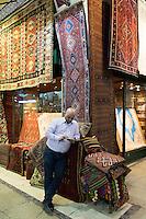 Shopkeeper using smartphone at Turkish carpet rug shop in The Grand Bazaar, Kapalicarsi, great market, Beyazi, Istanbul, Turkey