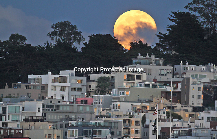 May's full moon rose over the Telegraph Hill as  seen from Aquatic Park Pier, SF., CA.