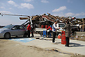 "March 29, 2011, Minamisanriku, Miyagi, Japan - More than two weeks after the tsunami the rural area between Kesennuma and Minamisanriku lies in ruin. Masashi Takahashi is one of the last customers at the JA Minamisanriku gas station operated by Masako Oyama. ""We just opened in September. What now?  Who knows?"" She laughed. (Photo by Wesley Cheek/AFLO) [3682]."