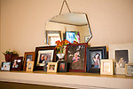 Photos of family and friends line the fireplace mantel in the living room of Margaret B. Jones