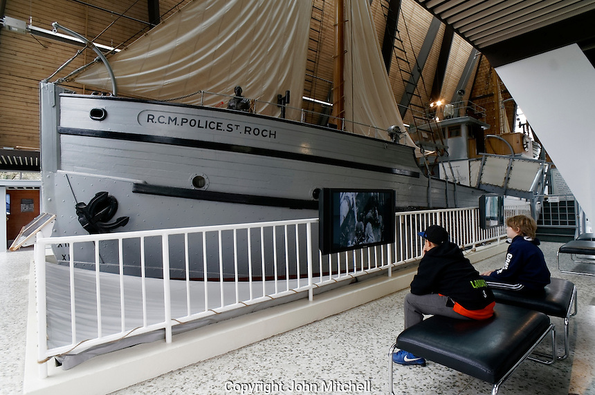 Two boys watching an interpretive video next to the RCMP St. Roch schooner, Vancouver Maritime Museum, Vancouver, BC, Canada