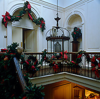 Festive green and red garlands with gold pine cones  hang from doorways and the balustrade around the stairwell
