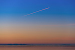 The contrail of a glinting jetliner is turned orange by the sunset as it takes off from Victoria, BC. and soars over the Puget Sound.