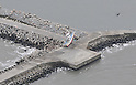 February 26, 2012, Fukushima, Japan - A fishing boat pushed by the tsunami over the breakwater near the town's harbor, is pictured in this aerial photo taken from a Mainichi helicopter on Feb. 26, 2012 in Namie, Fukushima Prefecture.