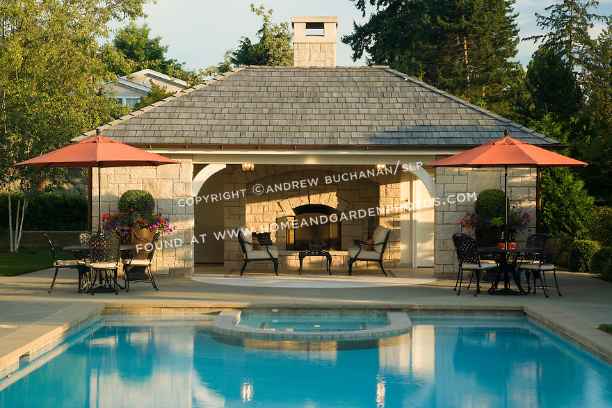 A poolside cabana building with a built in outdoor fireplace sits peacefully at the end of a beautiful blue pool with a built in tiled spa glowing in the early evening sunlight, flanked by matching outdoor table and chairs with identical orange red outdoor umbrellas providing a complement to the blue of the pool.