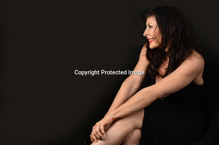 Stylish mature woman in evening gown stock photo