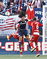 New England Revolution forward Juan Toja (7) attempts to head a crossed ball..  In a Major League Soccer (MLS) match, FC Dallas (red) defeated the New England Revolution (blue), 1-0, at Gillette Stadium on March 30, 2013.