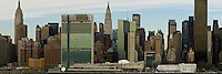 A panoramic photograph of New York City as seen from Long Island City, New York.  Many famous buildings are visible including the Chrystler Building, Empire State Building, Bank of America Tower, and many more.  You can also see the Ed Koch Bridge (formerly the 59th Street Bridge).
