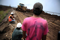 Workers continue building up the earthen dam, the only barrier that contains the rising lake of mud. Since May 2006, more than 10,000 people in the Porong subdistrict of Sidoarjo have been displaced by hot mud flowing from a natural gas well that was being drilled by the oil company Lapindo Brantas. The torrent of mud - up to 125,000 cubic metres per day - continued to flow three years later.