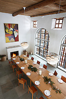 Aerial view of the dining room which has a double-height ceiling and a table that seats 24 in front of enormous windows