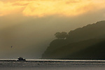 The sun rose over Angel Island as a loan fishing boat heads out to sea on San Francisco's Bay, California..