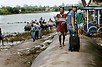 A young man looks back as he walks towards the rafts to cross the river. Despite the nearby international bridge of the offical border, many travelers who don't have visas choose the way of the river for just 10 quetzales. For most migrants, the journey really begins in Mexico where they will face the most dangerous part of migrating from Central America. Many face bandits and gangs who rob, rape or kill along the 1,500 mile path to al norte, or the north. On average, the journey from the Suchiate River to the U.S. border takes 15 days on 12 trains..