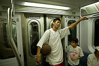 Members of the Far East Ballers, a Japanese street basketball team, ride back to their hotel in the subway after playing a game against a local team in the Rodney tournament in New York City, USA, June 19 2005.