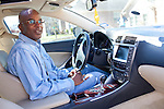 DNA Exonerated prisoner Thomas McGowan, sits in his Lexus luxury car at his home in Garland, Texas, while his girlfriend Kim Moses looks on from the background.