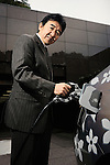 Yutaka Matsumoto, project general manager of Toyota Motor Corp.'s Strategy Planning Dept.'s R&D management center, inserts the recharger hose into one of the automaker's plug-in hybrid vehicles at the company's headquarters in Tokyo, Japan on Tuesday 11 March 2009.