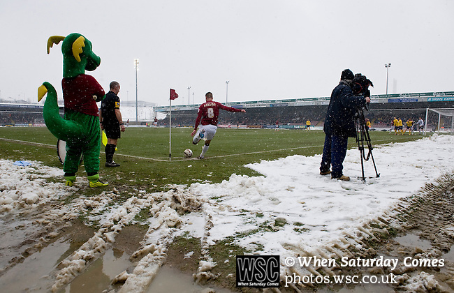 Northampton Town 1 Oxford United 0, 23/03/2013. Sixfields, League Two. Oxford United are the visitors to Sixfields as the long British winter continues in Northamptonshire. Clarence the Dragon and a TV cameraman watch from the slush as Northampston's Ben Harding takes a corner in the worsening conditions. Photo by Simon Gill