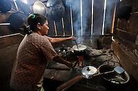 A woman using lamtoro wood to cook, Bangga, Gorontalo, Sulawesi, Indonesia.