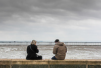 A couple sit on a wall on Southend seafront on a cloudy day.