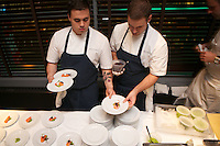 New York, NY - October 26, 2014: Cooks from Batard prepare small dishes at the opening reception for the International Chefs Congress, hosted by StarChefs at Urbo. <br /> <br /> CREDIT: Clay Williams for StarChefs.<br /> <br /> &copy; Clay Williams / claywilliamsphoto.com