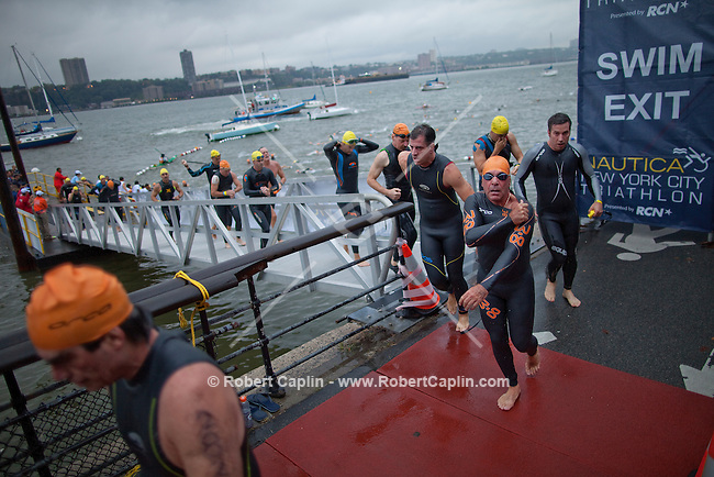 Triathletes exit the Hudson River and enter the biking phase of New York City Triathlon...Photo by Robert Caplin.