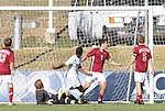 09 November 2010: NC State's Gbengha Makinde (in white) scores a goal after Virginia Tech's James Daly (in gray) had spilled the ball, tying the game 3-3. The North Carolina State University Wolfpack defeated the Virginia Tech Hokies 6-3 at Koka Booth Stadium at WakeMed Soccer Park in Cary, North Carolina in the ACC Men's Soccer Tournament Play-In game.