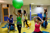 Women are exercising in a gym.