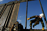 Private Thomas Carter of the 115th Group of the Utah National Guard hops the fence along the US-Mexico border while constructing it near San Luis, AZ on Wednesday, June 7, 2006.<br />