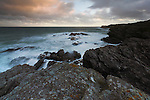 Sunset with rugged coast at Porth-y-Post, Anglesey, North Wales, UK