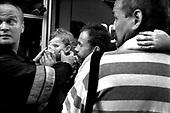 Wroclaw 14.04.2005 Poland..Children with an oxygen mask on fathers hand after fire...The worst and the most dangerous district in Wroclaw ( Poland ) , called by people &quot;The Bermuda Triangle&quot;. There are walls bearing an inscription &quot;Who will enter here, will not exit alive&quot; Many families there are pathological and live in extreme poverty. Children have no place for any games so they loaf around on this wasted district and disseminate a juvenile delinquency. Many of them become sexually active though thery are only 10-12 years old...(Photo by Adam Lach / Napo Images)<br /> <br /> Najbardziej nabezpieczna dzielnica we Wroclawiu zwana przez ludzi Trojkatem Bermudzkim. Sa tam sciany opatrzone napisem &quot; Kto tu wejdzie, nigdy nie wyjdzie stad zywy&quot; Mieszka tam wiele rodzin patologicznych i zyja w wielkiej nedzy. Dzieci wlocza sie po ulicach nie majac miejsc na zabawe i szerza przestepczosc wsrod nieletnich. Wiele z dzieci uprawia seks choc maja zaledwie 10-12 lat...(Fot Adam Lach / Napo Images)