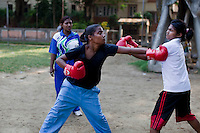 Razia Shabnam (in blue tshirt and track pants) conducts a boxing training session with a group of girls from an NGO in a park in Basduni, Tolly Gunge, Calcutta, West Bengal, India. Razia Shabnam, 28, was one of the first women boxers in Kolkata. She was also the first woman in her community to go to college. She is now a coach and one of only three international female boxing referees in India.  Photo by Suzanne Lee for Panos London