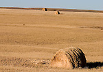 Several bales of hay dot the golden hills of far northwestern Nebraska on a warm fall day.