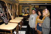 Curator Landon Knox, 16, with guests, view the art exhibited at the 'On Board For The Bay' Art Show and Silent Auction at The Victorian on Sunday, October 23, 2011. 100% of Proceeds will benefit Heal the Bay.