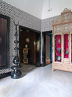 The walls of the entrance hall are covered in a Hexagon wallpaper by Cole & Son and a floor of Carrara marble. An ornately inlaid cabinet houses a collection of ceramics and glassware
