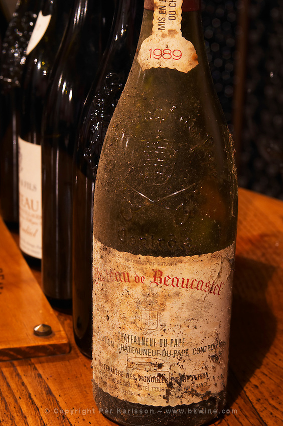 Old and dusty bottle of Chateau de Beaucastel Chateauneuf-du-Pape 1989 on a tasting table in the wine cellar of Domaine de Beaucastel Chateau de Beaucastel, Domaines Perrin, Courthézon Courthezon Vaucluse France Europe