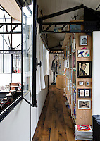 An interior window opens out to the atelier below from the long corridor running alongside