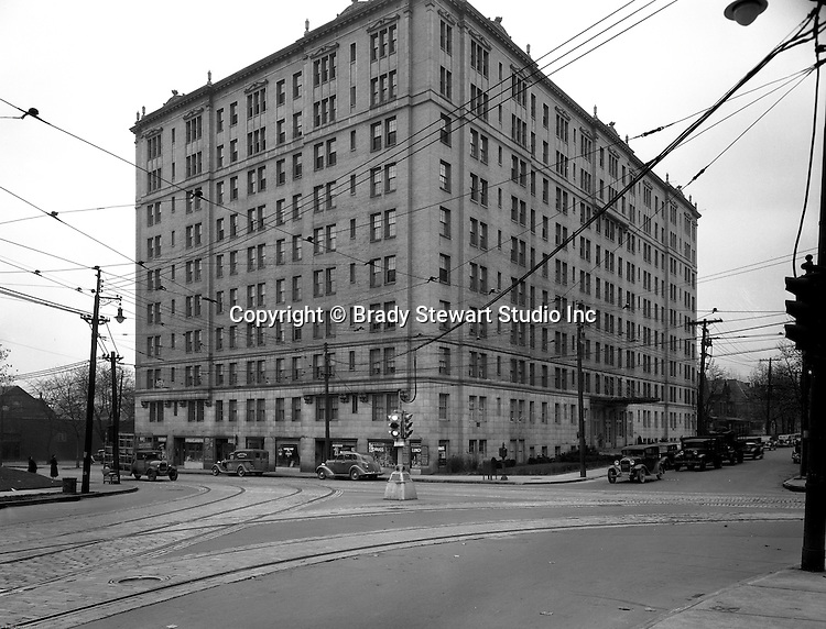 Pittsburgh PA:  View of the Arlington Apartments and Centre Avenue in Shadyside - 1935.  The apartments were built in the early 1900s and has businesses on the first floor; Arlington Pharmacy , Muller's Delicatessen, Arlington Coffee Shop, and Adell's Beauty Shop. Apartments are still in use today and primarily houses Pitt and Carnegie Mellon Students