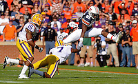 Daily Photo by Gary Cosby Jr. <br /> <br /> Auburn receiver Terrell Zachery leaps over LSU tackler Patrick Peterson as Brandon Taylor closes on the play as Auburn played LSU in an SEC west showdown of unbeaten teams Saturday in Auburn.