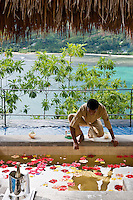 An outdoor bath is filled with floating flowers by one of the hotel attendants