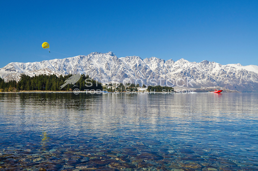 Tandem Para-sailing on Lake Wakatipu with snow covered Remarkables mountains behind, South Island, New Zealand.