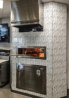 This custom commercial pizza oven features Forks Knives and Spoons, a handmade mosaic shown in Moonstone jewel glass from the Erin Adams Collection for New Ravenna.<br />