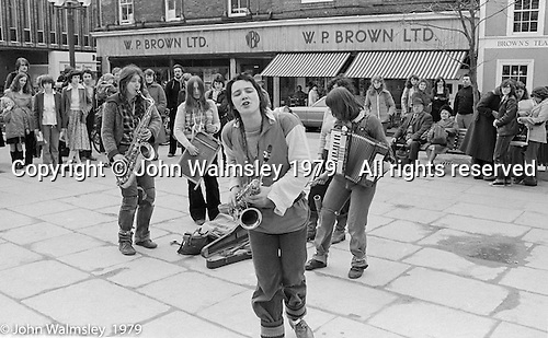 The York Street Band playing in York, March 1979.  Dena Attar on saxophone, Sarah Kemp on washboard, then the three members of the YSB: Ros Davies (saxophone), Sarha Moore (tambourine) hidden and Anthea Gomez (accordian).  Sarha Moore and Ros Davies went on to play in The Bollywood Band, and Ros also joined the Grand Union Band, in London.  Anthea Gomez went on to write and play music for the theatre and then BBC Drama before changing direction.