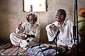 71 year old, Atam Khan, the older brother of 66-year-old Manganiyar artist, Lakha Khan (right) enjoy the field recordings of their performance in their house in Raneri village of Jodhpur district in Rajasthan, India. Photo: Sanjit Das/Panos